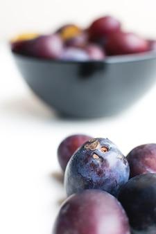 Particolare fresco delle prugne organiche su una priorità bassa bianca