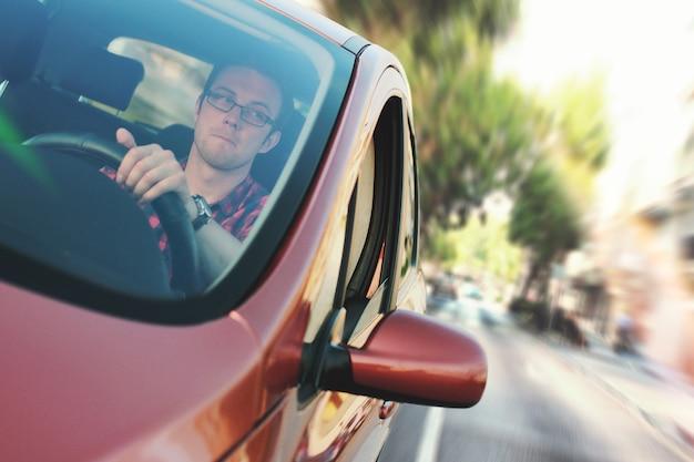 Particolare sul giovane conducente dentro in automobile in movimento
