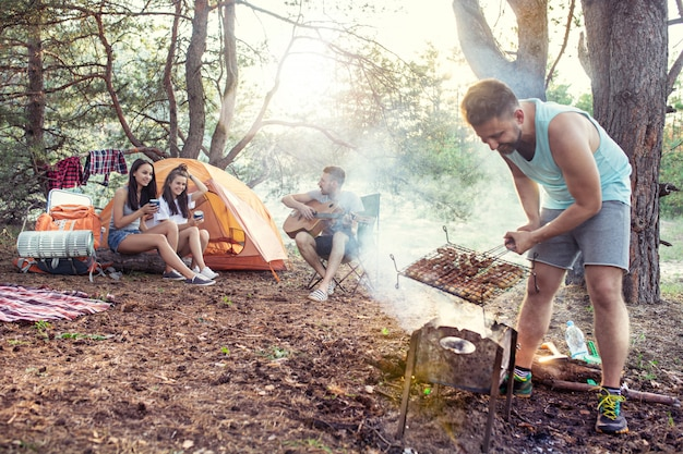 Partito, campeggio di uomini e donne gruppo nella foresta. si rilassano, cantano una canzone e cucinano il barbecue
