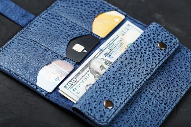 Partman in pelle blu con banconote da cento dollari e carte di credito elettroniche su un muro nero