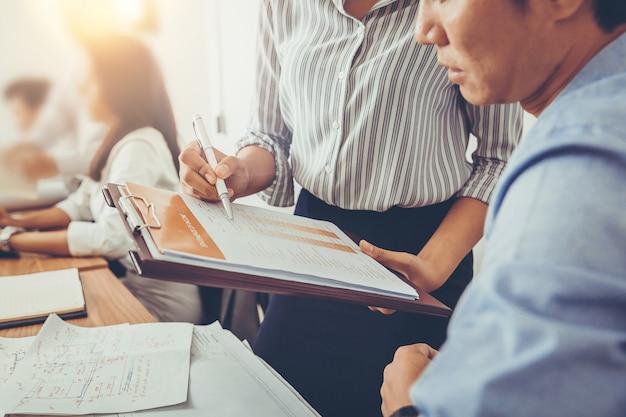 Partner commerciali che discutono di documenti e idee che pianificano un nuovo progetto durante la riunione.