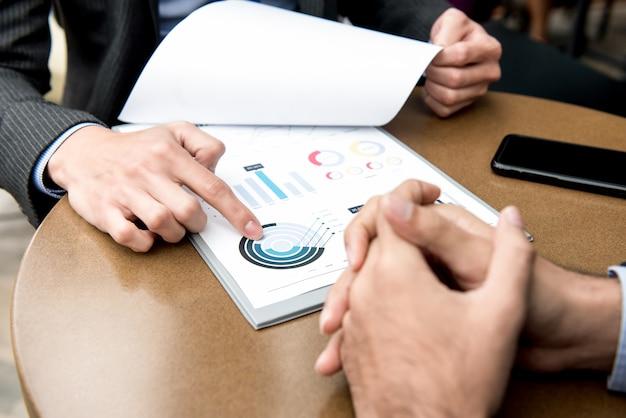 Partner commerciali discutendo grafici finanziari