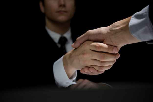 Partner commerciali facendo stretta di mano in ombra scura