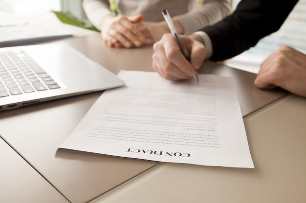 Partner commerciali femminili e maschii che firmano contratto