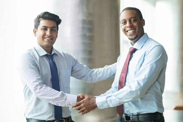 Partner commerciali multietnici felici che agitano le mani