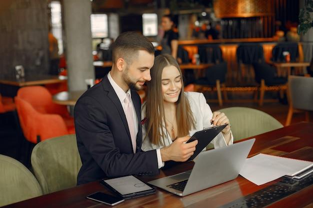 Partner seduti al tavolo e che lavorano in un caffè