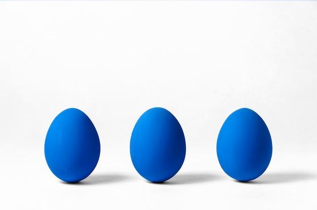 Pasqua creativa. tre uova su bianco. concetto di minimalismo. colore alla moda dell'anno - blu classico. copia spazio