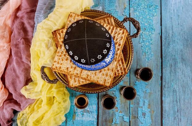 Pasqua ebraica matzoh pane festa ebraica con kipah e quattro tazze di vino sul tavolo di legno.