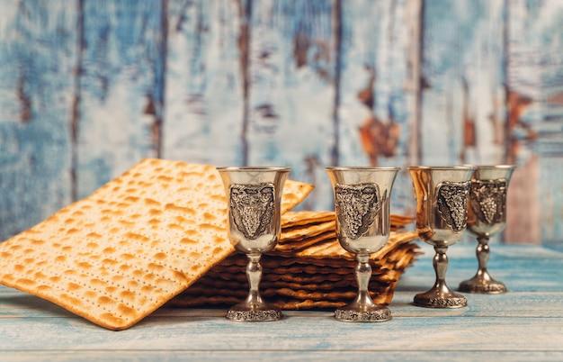 Pasqua ebraica quattro bicchieri di vino e pane matzoh festa ebraica su tavola di legno.