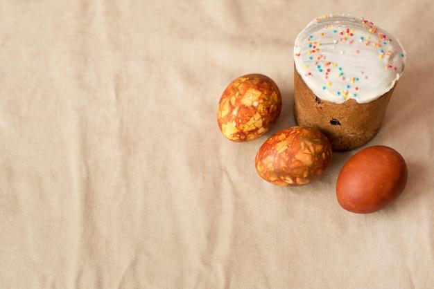 Pasqua ha dipinto le uova e la torta su sfondo beige chiaro con uno spazio di copia
