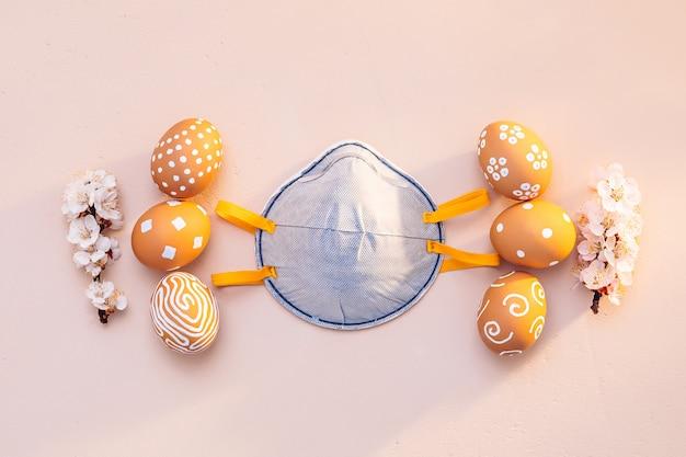 Pasqua in un periodo di pandemia. uova di pasqua con rami di albicocca fioritura e una maschera protettiva