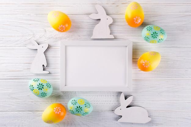 Pasqua mock up con cornice per foto. uova di pasqua colorate e coniglietto in legno decorativo. celebrazione, concetto di vacanza. vista piana, vista dall'alto, copia spazio