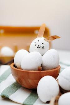 Pasqua, uovo decorato con la faccia di coniglio e altre uova bianche in ciotola di legno e vassoio di uova sul panno a strisce verde e bianco