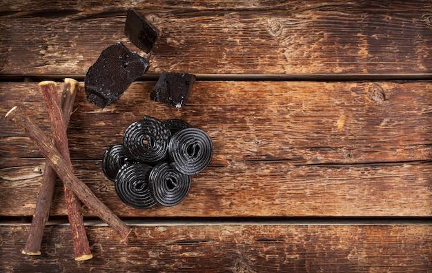 Passaggi di produzione di liquirizia, radici, blocchi puri e caramelle.