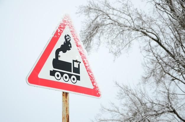 Passaggio a livello senza barriera. un cartello stradale raffigurante una vecchia locomotiva nera