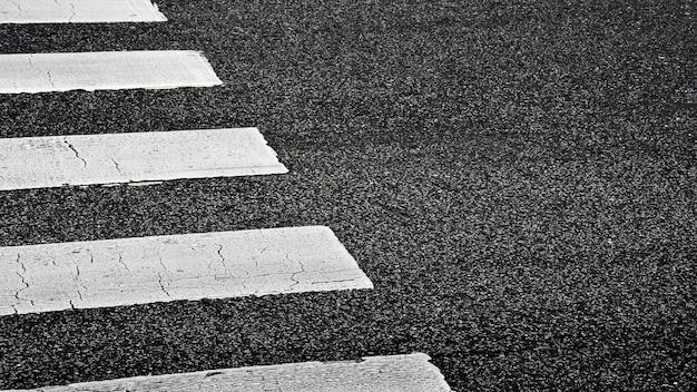 Passaggio pedonale della zebra su una strada asfaltata - fondo del primo piano