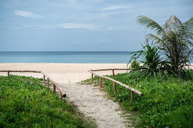 Passaggio pedonale sabbioso alla spiaggia del mare sul fondo del cielo blu