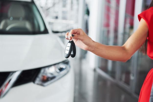 Passando le chiavi della macchina. primo piano potato di un commerciante di automobile che dà le chiavi dell'automobile