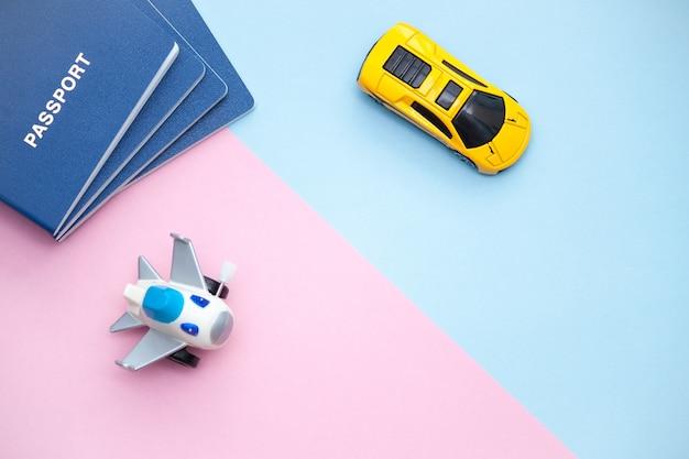 Passaporti, aereo e auto su cartone rosa e blu