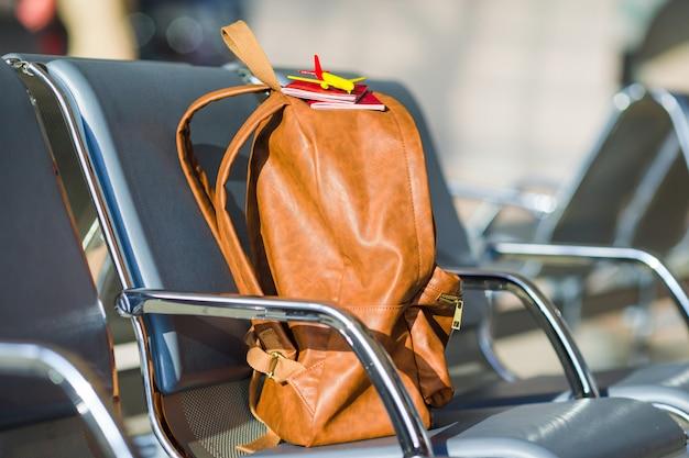 Passaporti del primo piano e modello dell'aeroplano sullo zaino all'aeroporto
