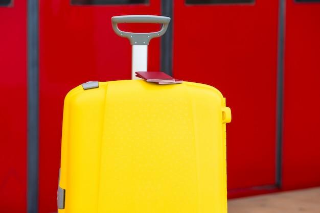 Passaporti rossi del primo piano su bagagli gialli alla stazione ferroviaria