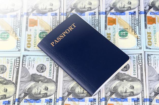 Passaporto blu con centinaia di dollari di banconote, affari o concetto di viaggio.