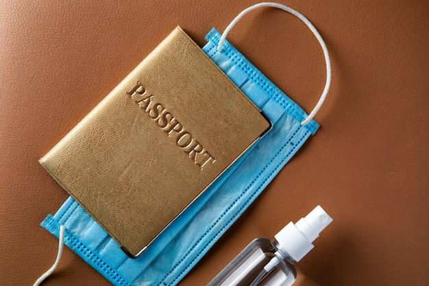 Passaporto con mascherina medica, spray disinfettante per mani sul tavolo