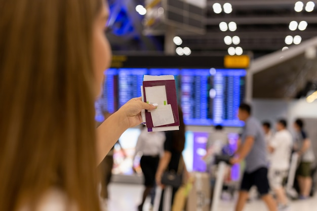 Passaporto della tenuta della mano della donna e passaggio di imbarco all'aeroporto nel fondo della sfuocatura.