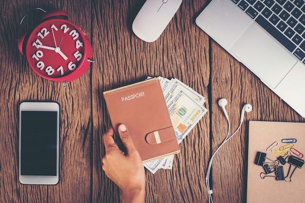 Passaporto di vista superiore con soldi sull'area di lavoro, concetto di turismo