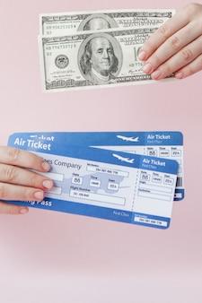 Passaporto, dollari e biglietto aereo in mano della donna su uno sfondo rosa. concetto di viaggio, copia spazio