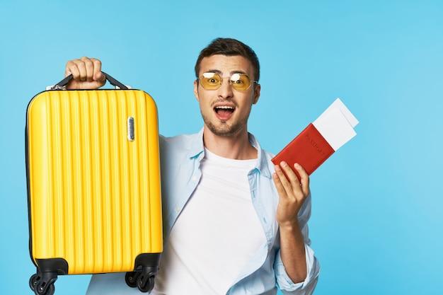 Passaporto e biglietti aerei bagagli giallo valigia passeggero uomo con gli occhiali viaggio aeroporto volo