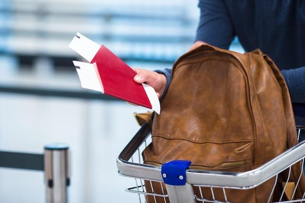 Passaporto e biglietto d'imbarco e uno zaino nei carrelli portabagagli