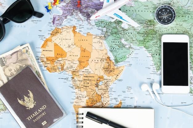 Passaporto e soldi dello smartphone con la bussola sulla mappa per il programma di viaggio