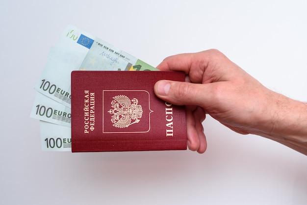 Passaporto internazionale russo con euro nella mano dell'uomo