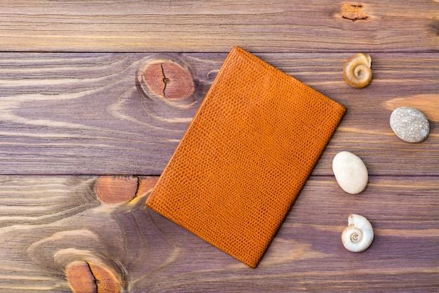 Passaporto, pietra e conchiglie su un fondo di legno