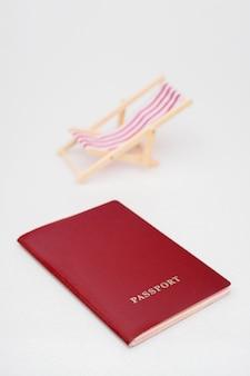 Passaporto rosso e sedia a sdraio rossa su sfondo bianco.