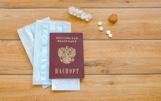 Passaporto russo con la scritta covid-19, maschere protettive e compresse