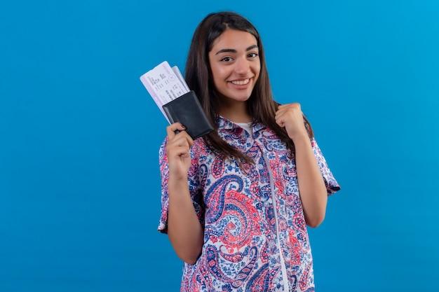 Passaporto turistico della giovane bella donna che tiene con i biglietti che sembrano usciti rallegrandosi del suo successo e della vittoria stringendo il pugno con gioia felice di raggiungere il suo scopo e gli obiettivi in piedi sopra l'isolato