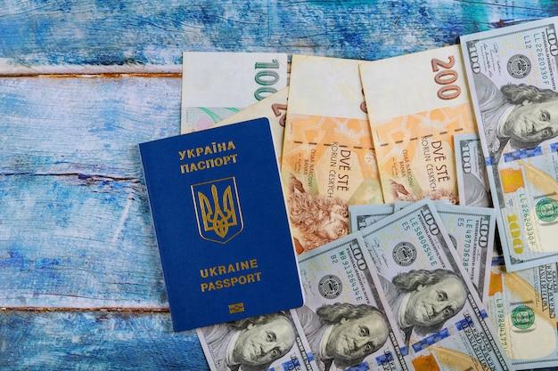 Passaporto ucraino con banconote da cento dollari e banconote in corone ceche