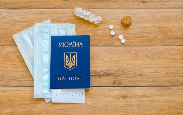 Passaporto ucraino con la scritta covid-19, maschere e compresse protettive