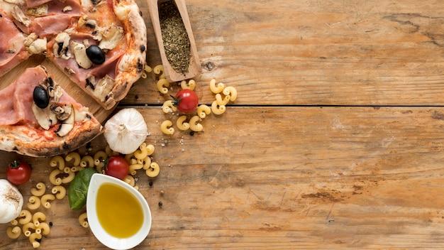 Passato maccheroni crudo; pizza al forno e ingredienti freschi sulla tavola di legno