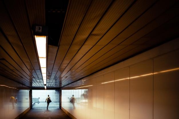 Passeggeri in fretta alla fine di un tunnel all'ingresso della stazione della metropolitana.