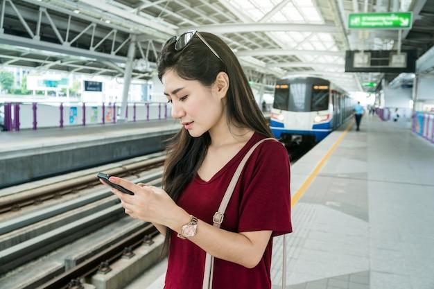 Passeggero asiatico della donna con il vestito casuale facendo uso della rete sociale tramite il telefono cellulare astuto nel bts sk