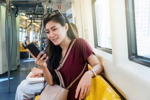 Passeggero asiatico della donna con il vestito casuale facendo uso della rete sociale tramite il telefono cellulare astuto