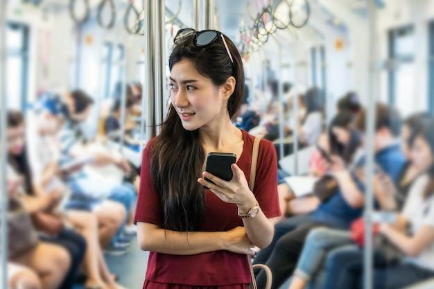 Passeggero asiatico della donna con il vestito casuale facendo uso della rete sociale