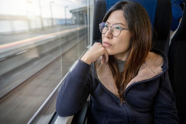 Passeggero asiatico della giovane signora che si siede in un umore depresso accanto alla finestra dentro il treno