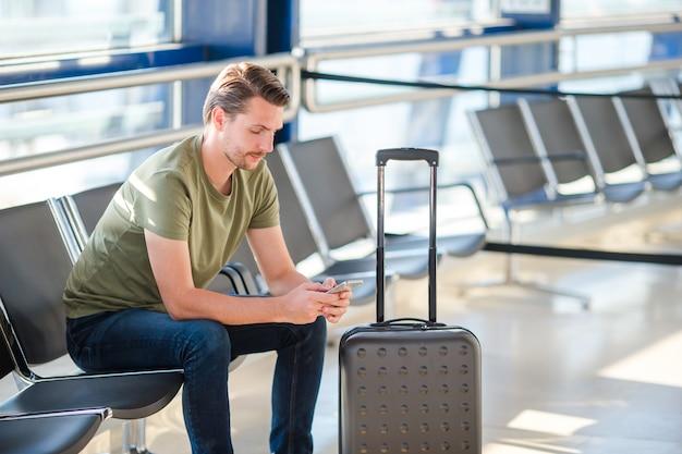 Passeggero in una sala dell'aeroporto in attesa di volo aereo, giovane uomo con cellulare in aeroporto in attesa di atterraggio