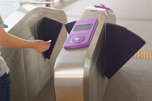 Passeggero usa il biglietto della moneta touch con la barriera di accesso automatica