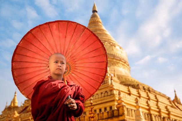 Passeggiata del monaco buddista birmano con umbella nella pagoda dorata di shwezigon paya