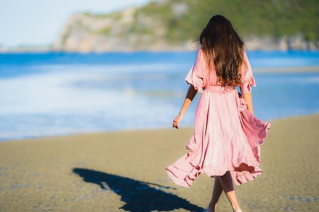 Passeggiata felice di sorriso della bella giovane donna asiatica del ritratto sul mare all'aperto tropicale della spiaggia della natura